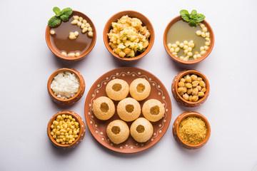 Pani Puri is Indian chat item served in a terracotta bowls and plate
