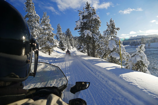Rider snowmobiling in Yellowstone National Park, Wyoming, United States