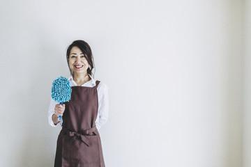 掃除道具を持っている笑顔の主婦
