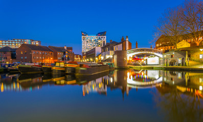 The cube behind brick buildings alongside a water channel in the central Birmingham, England Wall mural