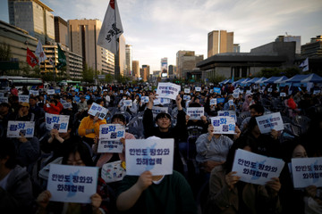 People hold placards during a rally to wish for a successful inter-Korean summit, in central Seoul
