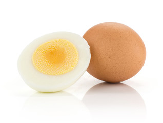 One brown chicken egg and boiled sliced half isolated on white background.