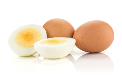 Two brown chicken eggs with boiled sliced halves isolated on white background.