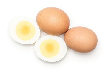 Two brown chicken eggs with boiled sliced halves top view isolated on white background.