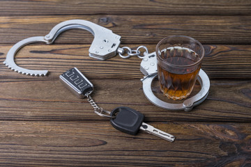 Concept of alcohol driving. Car keys, a glass of whiskey and handcuffs, The idea of arrest is a drunken pusher behind the wheel.