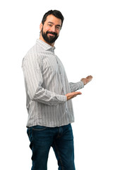 Handsome man with beard presenting and inviting to come