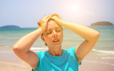 Woman on hot beach with sunstroke. Health problem on holiday. Medicine on vacation.