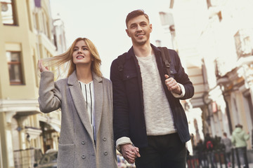 Young couple walk at the street on sunny day