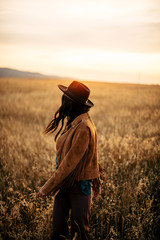 Boho nomads girl in field at Sunset
