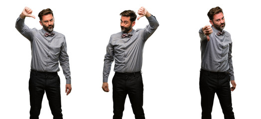 Middle age man, with beard and bow tie showing thumbs down unhappy sign of dislike, negative expression and disapproval