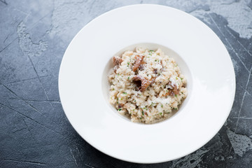 Risotto with chanterelles and parmesan cheese served in a white plate on a grey concrete background