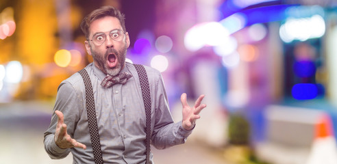Middle age man, with beard and bow tie happy and surprised cheering expressing wow gesture at night club