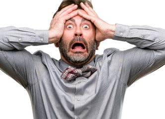 Middle age man, with beard and bow tie stressful keeping hands on head, terrified in panic, shouting isolated over white background