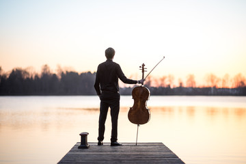 Cello cellist musician playing music as professional in summer while sunset, very relaxing