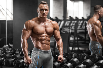 Muscular man working out in gym, strong male naked torso abs Wall mural