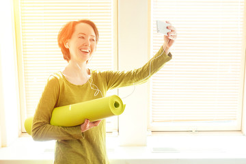 cheerful brunette woman in a green blouse holds a roll of mate and makes selfie on the phone near the window in a yoga class. smartphone in the hands of a yoga coach