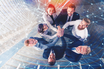 Business people putting their hands together with internet network effects. Concept of integration, teamwork and partnership. double exposure