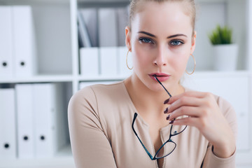 Sexy secretary with glasses in hand undresses in office, flirt and desire. Office provocation.
