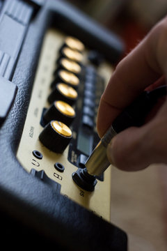 Closeup of man's hand plugging jack into the guitar amplifier