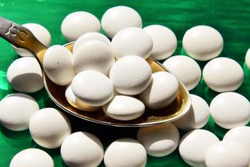 таблетки белого цвета лежат на ложке из золота на зеленом фоне