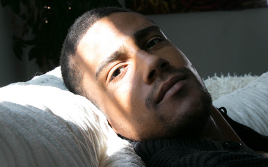Portrait of a handsome, good looking black man lying down