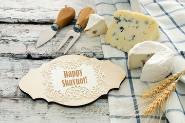 image of dairy products over white wooden planks background. Symbols of jewish holiday - Shavuot.