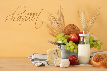 image of fruits, bread and cheese in the basket over wooden table.