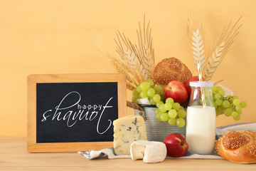 image of fruits, bread and cheese in the tin basket over wooden table.