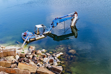 Drowned excavator in old abandoned basalt quarry