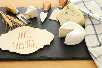 image of dairy products over black stone slate background. Symbols of jewish holiday - Shavuot.