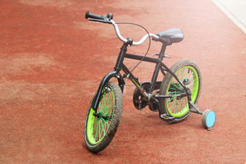 Green children's bike at sunset.