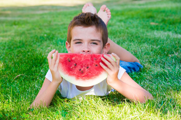 Child eating juicy watermelon outdoors on grass