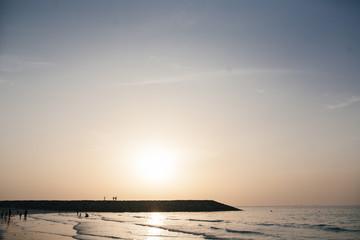 Sunset on the sea coast. People on vacation