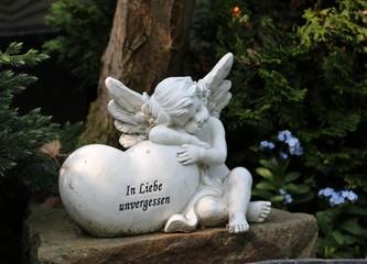 Engel ruht auf einem Grab mit Herz neben Vergissmeinnicht