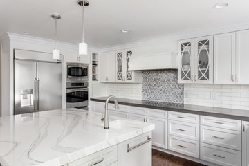 Kitchen in New Luxury Home with White Cabinets, Stainless Steel Appliances, and Large Island with Sink