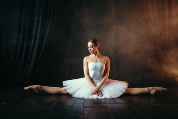 Ballerina in white dress sits on a twine