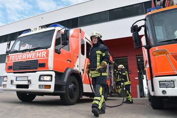 Feuwehrwehr: Feuerwehrmänner am Löschfahrzeug vor dem Einsatz zur Bekämpfung eines Brandes an der Feuerwache // Fire brigade: firefighters at the fire station