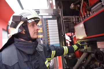 Feuerwehrmann bedient Technik am Löschfahrzeug zur Bekämpfung von Hausbränden // Firefighter operates technology on fire engine to fight house fires