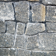 The texture of a stone fence made of granite. Background