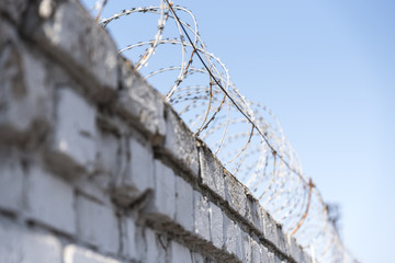 Barbed wire on a brick fence