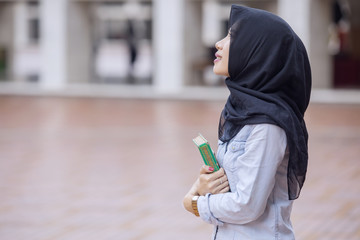 Pretty girl carrying a Quran in the mosque