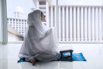 Muslim woman prays to the Allah at home