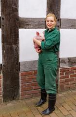 Image in der Schweinehaltung, junge Bäuerin mit Ferkel im Arm