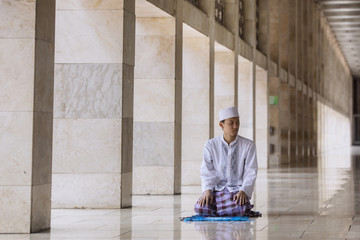 Asian Muslim man doing Salat on the mosque