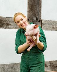 Werben für artgerechte Tierhaltung, junge Landwirtin hält ein Ferkel im Arm