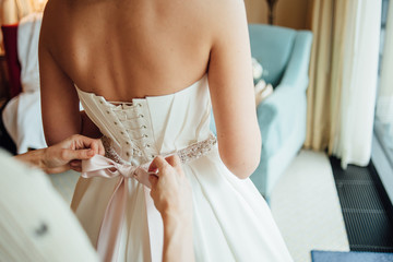 Hands tie a bow from a pink satin belt with crystals on a white bridal wedding dress, horizontal
