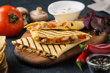 Mexican traditional food: chicken quesadilla with tomatoes