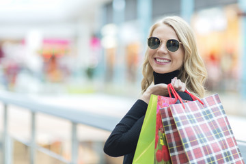Beautiful stylish young woman in sunglasses with shopping bags, place for your text on the left