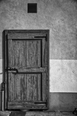 Ancient door in monochrome color, cracked wooden entrance, sample for post card