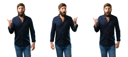Young man with beard happy and surprised cheering expressing wow gesture pointing up isolated over white background